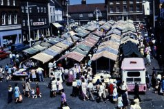 A view over the Market Place (probably in the 1960s) looking north, and taken from the first floor of the Woolworth's premises (the tall building in the distance in the other photograph).