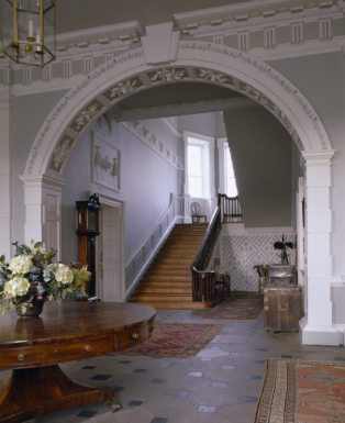 View of the Entrance Hall at Florence Court looking towards the cantilevered staircase. An entablature with a frieze of triglyphs run around the hall, supported by rusticated Doric Pillars.