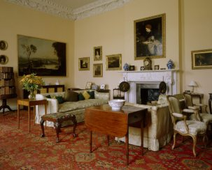 Drawing Room at Florence Court. The chimneypiece is neoclassical Carrara marble with Ionic columns & elaborate frieze. The room is filled with Enniskillen family portraits and furnishings.