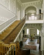 The staircase at Florence Court showing the inner hall with pediment and pendant frieze and the cantilevered staircase with fluted pearwood banisters and polished yew handrail.